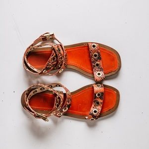 Ankle strap sandals with grommets detail.